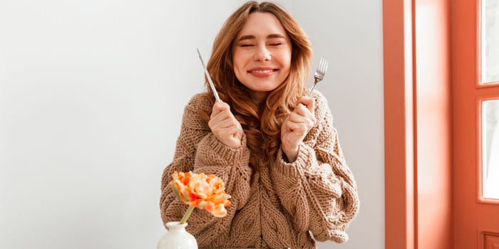 Femme souriante tenant des couverts