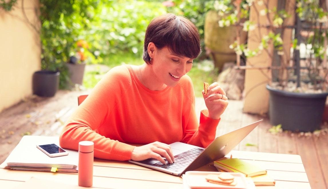 Femme travaillant sur son ordinateur portable avec biscuit Gerlinéa à la main
